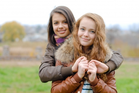 eachother: Two young best teenage girlfriends female women hugging eachother outdoors on autumn day