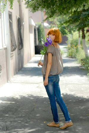 Beautiful redhead teenage girl with purple rose by green leaves background photo