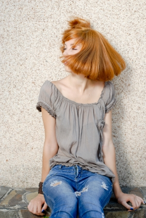 Young happy redhead teenage girl playing with hair Stock Photo