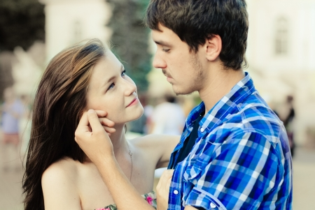 Happy young teenage couple man and woman in love looking at each other tenderly  in city