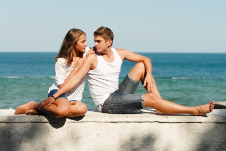 couple in summer: Young happy couple man and woman embracing on sea coast