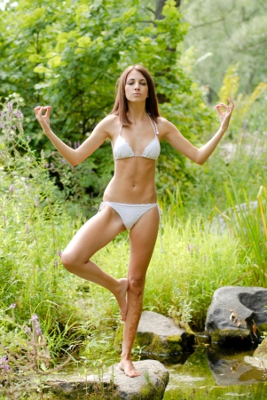 swimsuite: Young beautiful woman in white swimsuite in savage forest doing yoga