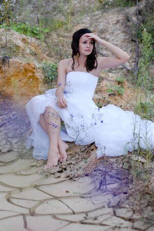 beautifull woman: Young beautiful bride sitting in desert Stock Photo