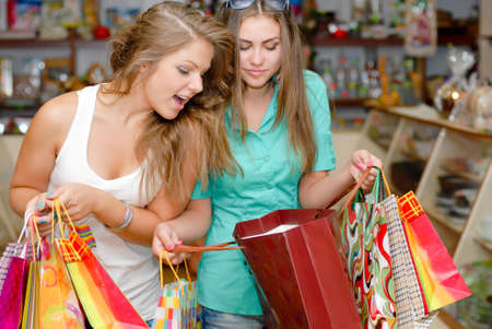 Two happy young women with shopping bags inside shop photo