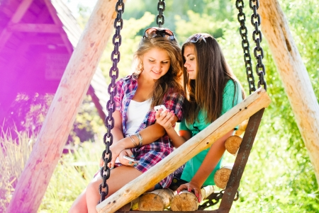 Two young girl friends sitting on swings in park and looking on mobile phone photo
