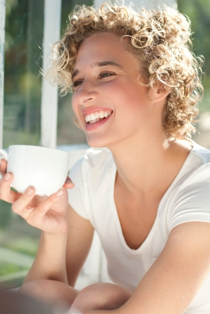 Young happy woman having morning cup of coffee by the window photo