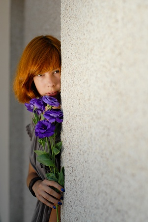 Young beautiful red hair woman holding purple chinese rose copy space photo