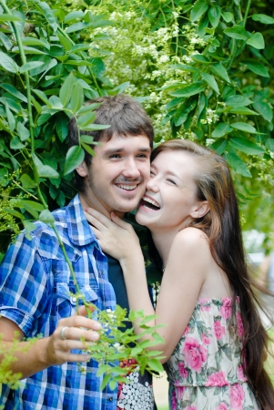 beautifull woman: Young happy smiling teen couple embracing on green park background Stock Photo