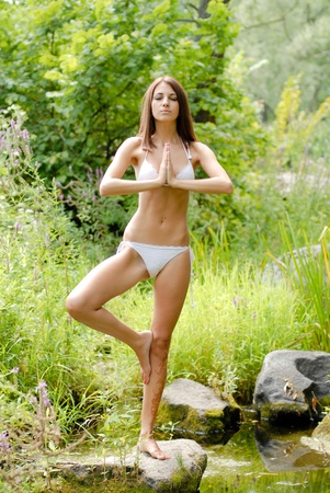 Young beautiful woman in white swimsuite in savage forest doing yoga photo