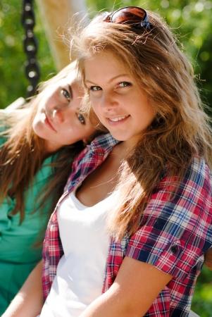 due amici: Due giovani amici ragazza seduta su altalene nel parco Archivio Fotografico