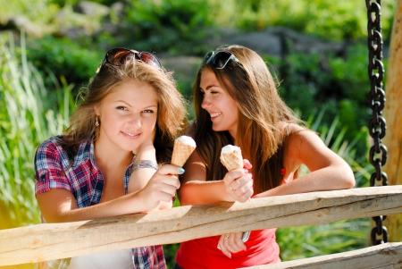 eating ice cream: Dos amigos felices chica adolescente al aire libre comiendo helado