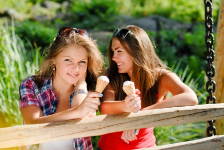 Two happy teenage girl friends eating ice cream outdoors photo