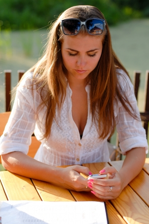 Unhappy seriuos teenage girl woman female looking at mobile phone photo