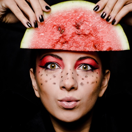 Young beautiful woman and watermelon portrait isolated over black photo