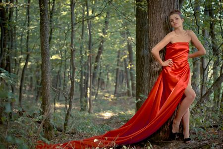Young beautiful woman in red dress in green woods photo