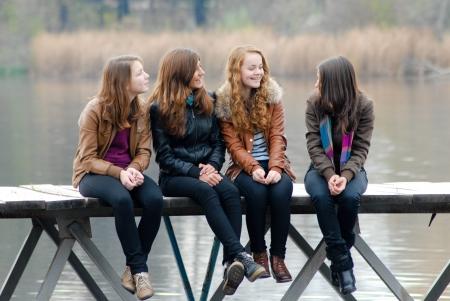 adolescentes chicas: Cuatro ni�as felices de la escuela que se sienta en el puente del r�o en el d�a de oto�o y mirando a otro lado Foto de archivo