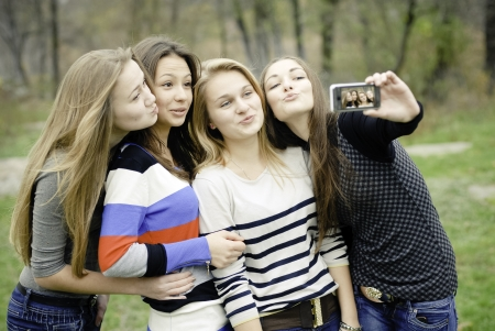 Four teen girls taking picture of themselves using tablet computer photo