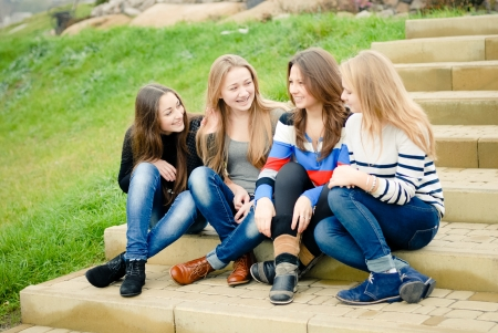 Four happy smiling teenage girls women female friends outdoors sitting on stairs photo