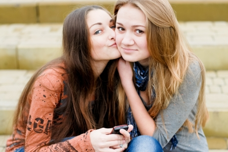 Teenage girl comforting her friend reading message photo