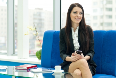 Young successful business female woman in formal suit smiling and holding mobile phone while sitting in office photo