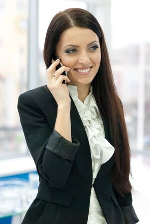 successfull: Young successfull business female woman in formal suit speaking on mobile phone by office window Stock Photo