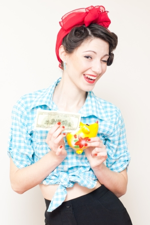 Retro pinup woman put money dollar note to porcelain mouse bank photo