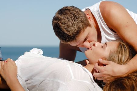 beautifull woman: Young happy vouple kissing by the sea Stock Photo