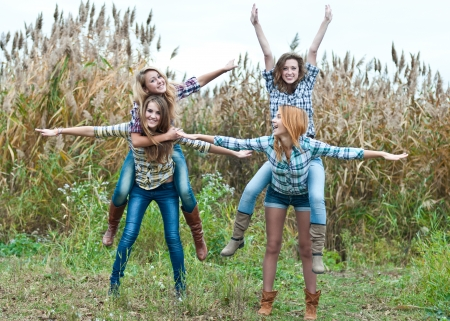 Four happy teen girls friends having fun outdoors photo