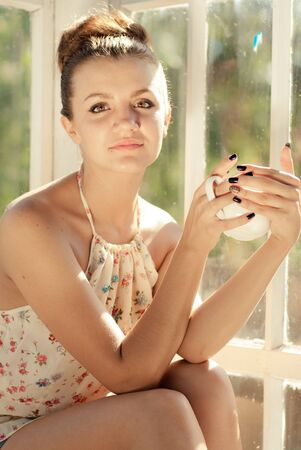 Young woman having morning cup of coffee by the window photo