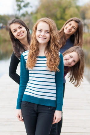 Four happy teenage girls friends Imagens