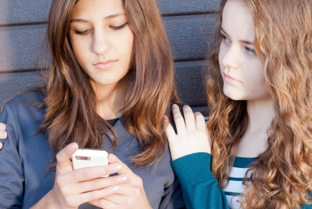 Teenage girl comforting her friend reading sad message Imagens