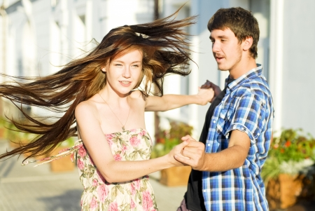 Young happy couple dancing on street photo