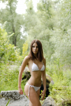 Young beautiful woman in white swimsuite in savage forest photo