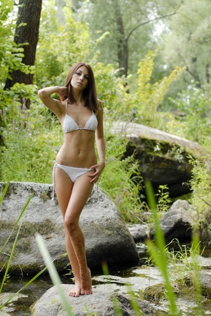 swimsuite: Young beautiful woman in white swimsuite in savage forest Stock Photo