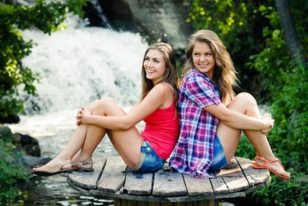 beautifull woman: Two teen girls sitting outdoors on summer day near waterfall
