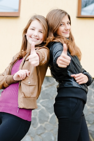 Two young girl friends showing thumbs up in autumn park photo