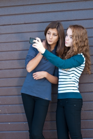 Two teen girls taking picture of themselves using tablet computer photo