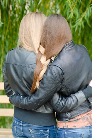 Two teenage girl friends having their long hair twisted photo