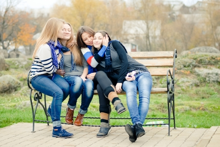 Four happy teen girls friends hugging and having fun outdoors photo