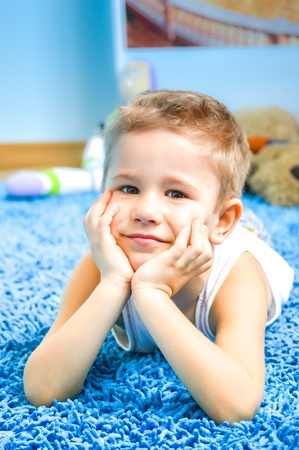 Happy kid  smiling boy on floor in living room at home Stock Photo - 18356358