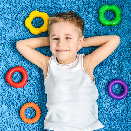 Happy kid  smiling boy on floor in living room at home photo