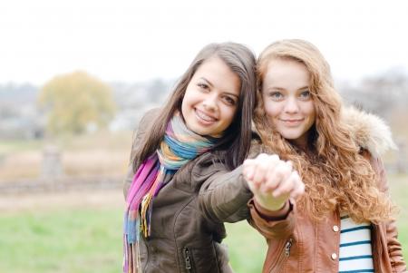 brunette and blond haired girls friends laughing and hug outdoors in spring or autumn