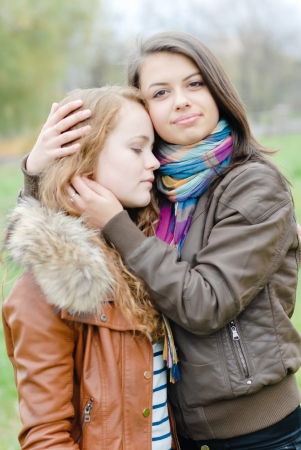 brunette and blond haired girls friends hugging outdoors in spring or autumn photo