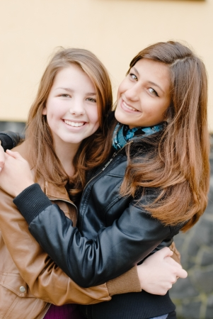 brunette and blond haired girls friends smiling, laughing and hug outdoors in spring or autumn photo