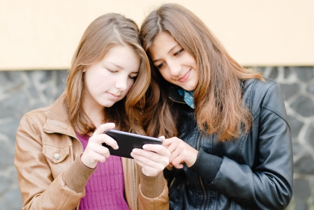 Two girls friends with mobile smart touch phone or other didgital gadget outdoors photo