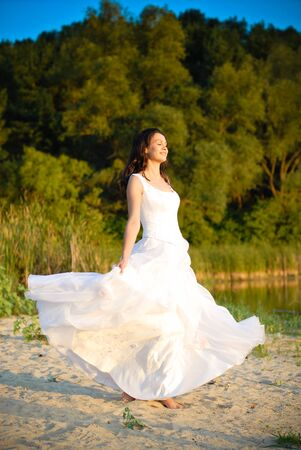 Bride standing at the riverside under tree sunset photo