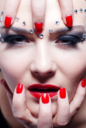 Beautiful young woman with bright red lips and manicure photo