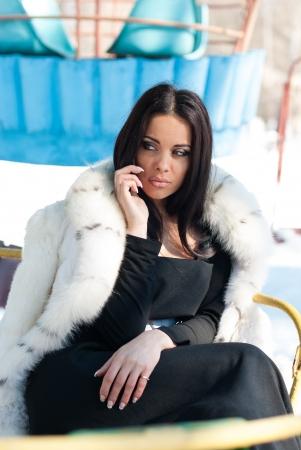 Winter Girl in Luxury Fashion Fur Coat on mobile phone photo