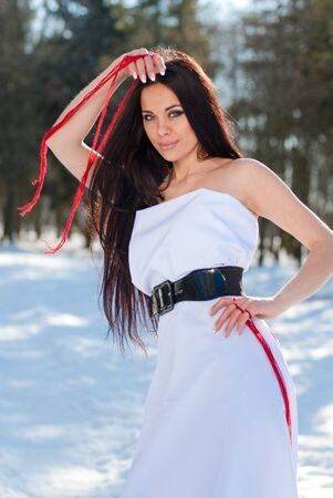 Sensual outdoor portrait of young beautiful brunette posing in snowy forest  photo