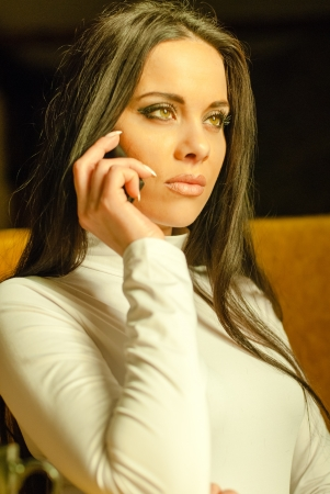 Attractive young businesswoman with phone in working process photo
